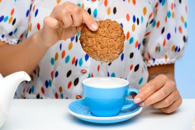 Close-up das mãos da mulher mergulhando biscoito no leite