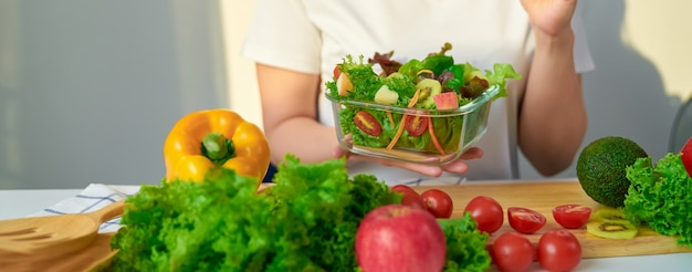 Close-up das mãos da mulher mostrando a saladeira e vários vegetais de folhas verdes na mesa em casa.