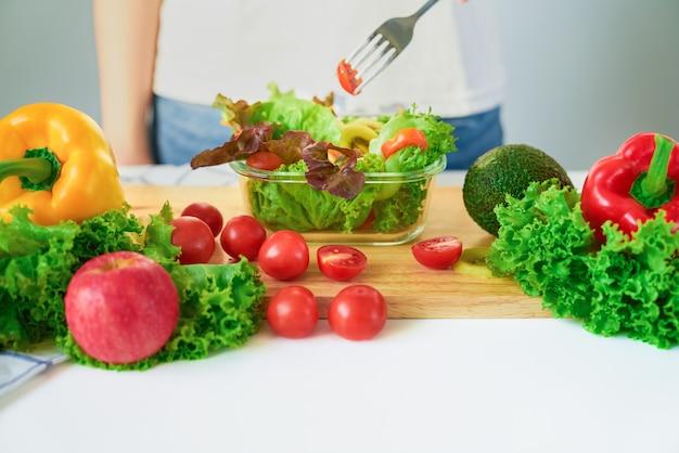 Close-up das mãos da mulher mostrando a tigela de salada e vários legumes com folhas verdes em cima da mesa na casa.