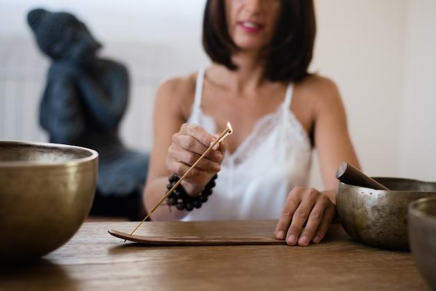 Close-up das mãos da mulher queimando um pau de incenso em sua sala de estar