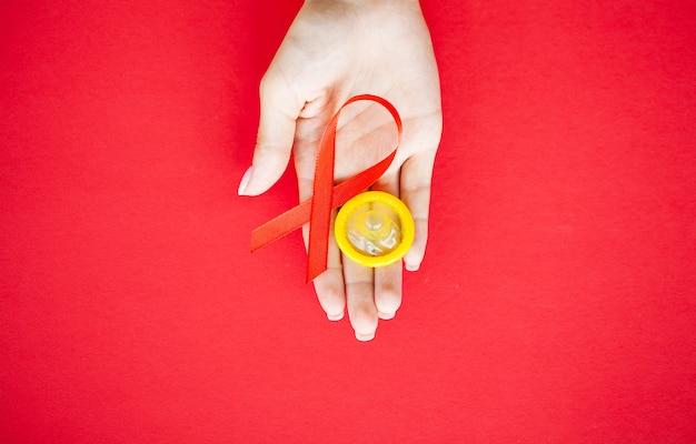 Close-up das mãos da mulher segurando uma fita vermelha e camisinha pedindo sexo seguro e atrás