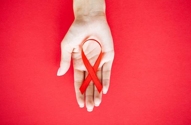 Close-up das mãos da mulher segurando uma fita vermelha pedindo sexo seguro e atrás