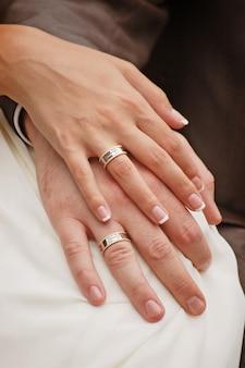 Close-up das mãos da noiva e do noivo com os anéis de casamento