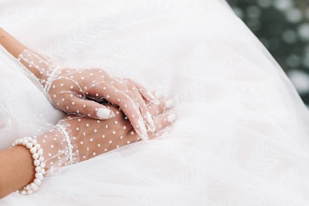 Close-up das mãos da noiva em luvas brancas transparentes perto de uma cachoeira no parque.