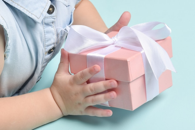 Close-up das mãos das crianças segurando um presente rosa com um laço branco sobre fundo azul.