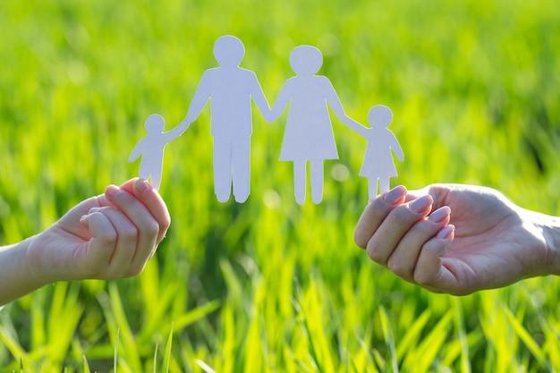 Close-up das mãos das pessoas, mostrando a família de papel na grama verde