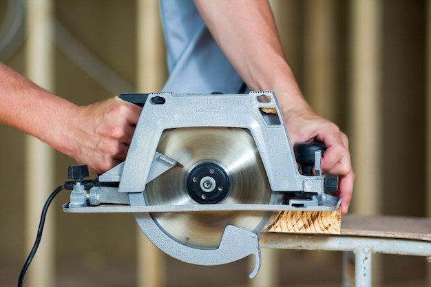 Close-up das mãos de carpinteiro muscular usando nova serra elétrica afiada circular poderosa moderna brilhante para cortar tábua de madeira dura. ferramentas profissionais para construção e construção de conceito.