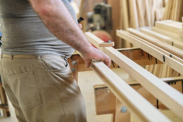 Close-up das mãos de carpinteiros com prancha de madeira na oficina de marcenaria de carpintaria.