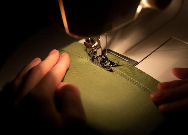 Close-up das mãos de mulheres em têxteis sob a agulha da máquina de costura