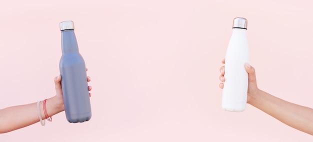 Close-up das mãos de mulheres segurando garrafas de água térmica de aço inoxidável reutilizáveis eco das cores branco e azul, no fundo da cor rosa pastel.
