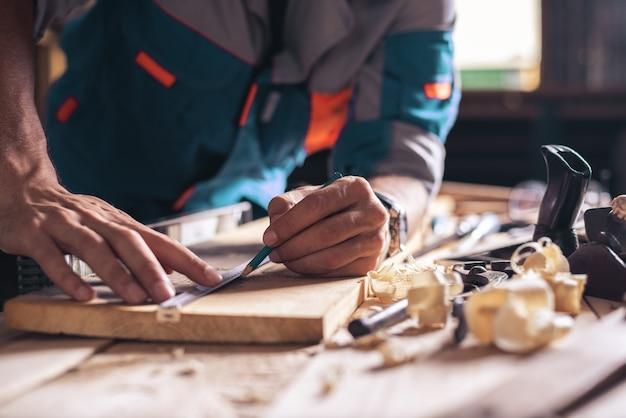 Close-up das mãos de um carpinteiro, um trabalhador com um lápis faz uma marca em uma placa de madeira.
