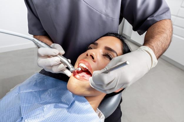 Close-up das mãos de um dentista com luvas limpando os dentes de um paciente em uma clínica