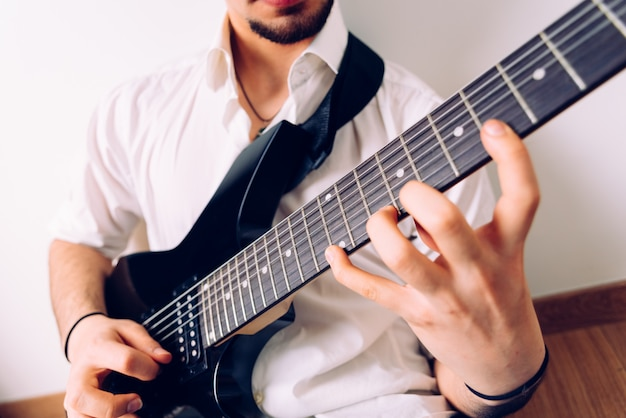 Close-up das mãos de um guitarrista tocando uma música enquanto pressiona as cordas.