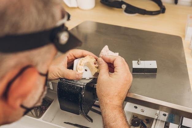 Close-up das mãos de um homem adulto, caucasiano, trabalhando em uma das peças de um molde de cerâmica em um laboratório de prótese dentária especializado em cerâmica óssea dentária para criar coroas de porcelana