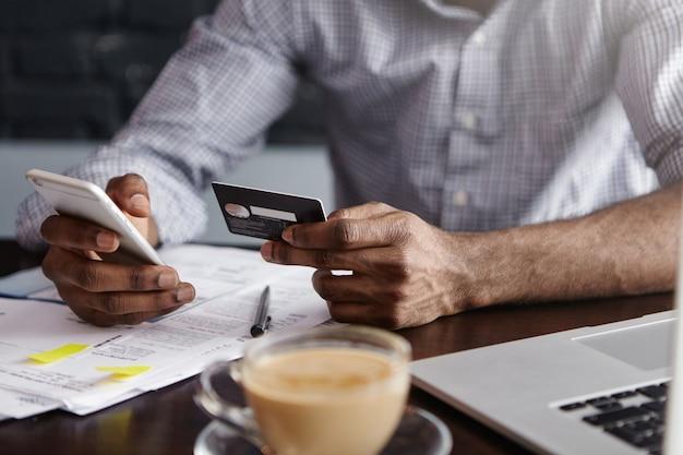 Close-up das mãos de um homem africano segurando um celular e um cartão de crédito