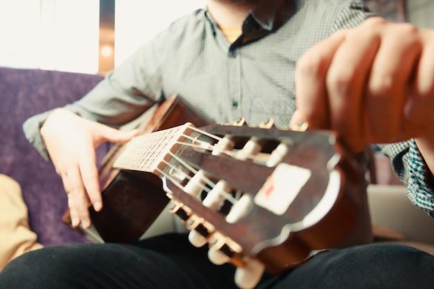 Close-up das mãos de um homem barbudo tocando violão espanhol em um dia ensolarado