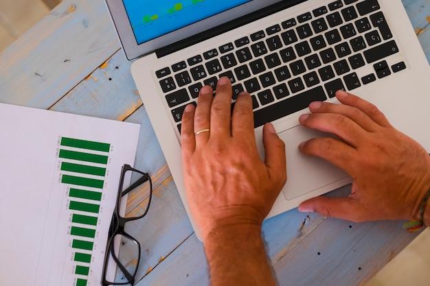Close-up das mãos de um homem em um laptop trabalhando arduamente para criar uma agitação - homem de negócios com gráficos no escritório ou em casa