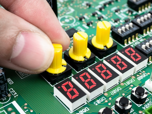 Close up das mãos de um técnico que verificam o pwb eletrônico (placa de circuito impresso) com a tecnologia do processador dos microchip