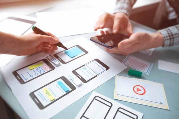 Close-up das mãos de um web designer, desenvolvendo aplicativos para interface de usuário de telefones móveis.