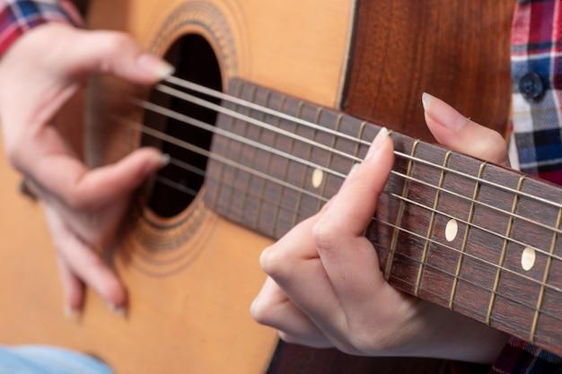 Close-up das mãos de uma jovem mulher tocando violão