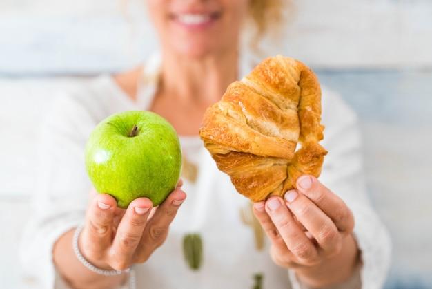 Close-up das mãos de uma linda mulher segurando um alimento saudável como uma maçã e, por outro lado, um alimento não saudável como um croissant