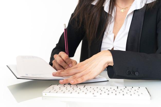 Close-up das mãos de uma mulher de negócios jovem vestida de terno e camisa branca, fazendo o trabalho de secretária na mesa do escritório no teclado do computador e escrevendo em um caderno