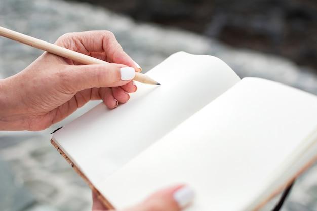 Close-up das mãos de uma mulher que escrevem em seu caderno com um lápis de madeira.