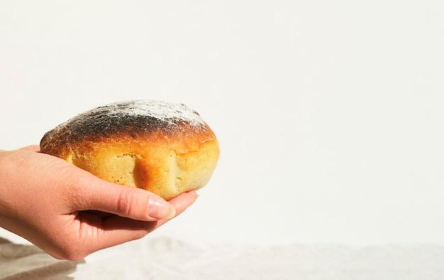 Close-up das mãos de uma mulher segurando pão acabado de fazer em casa. fundo branco. espaço para texto