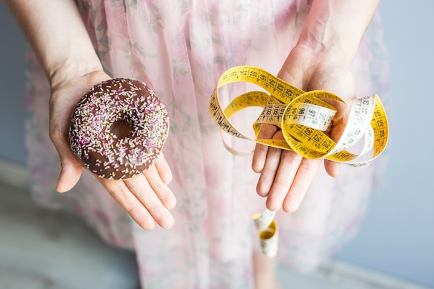 Close-up das mãos de uma mulher segurando uma rosquinha e uma fita métrica. o conceito de alimentação saudável. dieta.