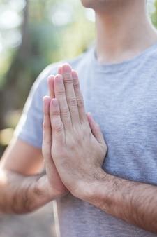 Close-up das mãos do adolescente no pose da ioga