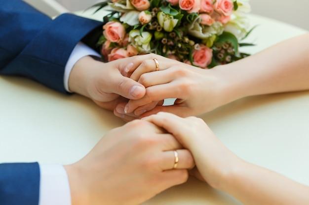 Close-up das mãos do casamento com anéis e buquê deitado na mesa