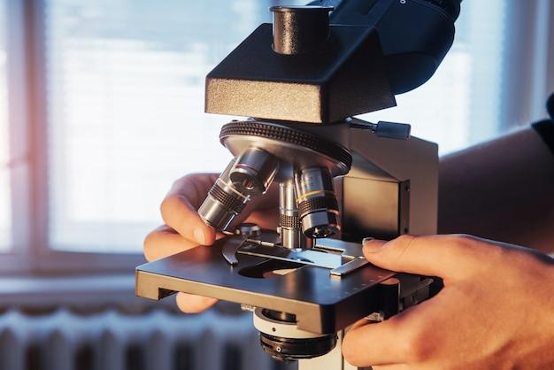 Close-up das mãos do cientista com microscópio, examinando amostras.