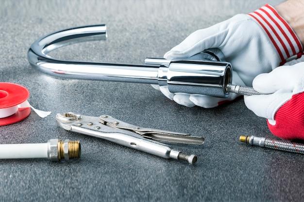 Close-up das mãos do encanador com torneira no fundo cinza do título. Foto Premium