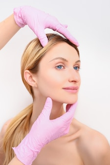 Close up das mãos do esteticista nas luvas que tocam na cara de jovem. conceito de cirurgia plástica. beleza facial. retrato de mulher loira bonita com maquiagem perfeita e pele macia e macia.