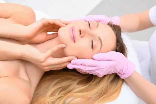 Close up das mãos do esteticista nas luvas que tocam na cara de jovem. conceito de cirurgia plástica. beleza facial. retrato de mulher loira relaxada bonita com os olhos fechados e pele macia e macia.