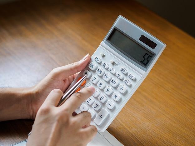 Close-up das mãos do homem está usando a calculadora na área de trabalho de madeira