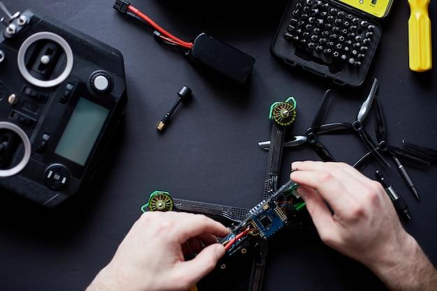 Close-up das mãos do homem montando um drone fpv de peças, usando ferramentas, preparando quadricóptero de corrida de alta velocidade para o vôo. repare o drone antes do processo de treinamento.