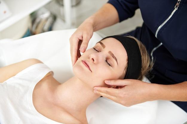 Close-up das mãos do médico cosmetologista massageando o rosto de uma jovem relaxada. massagem anti-envelhecimento lifting facial. massagem profissional de drenagem linfática em clínica de spa