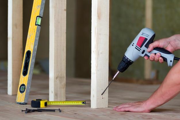 Close-up das mãos do trabalhador com chave de fenda no fundo de ferramentas profissionais