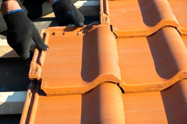 Close-up das mãos do trabalhador instalando telhas de cerâmica amarela montadas em placas de madeira cobrindo o telhado do edifício residencial em construção.