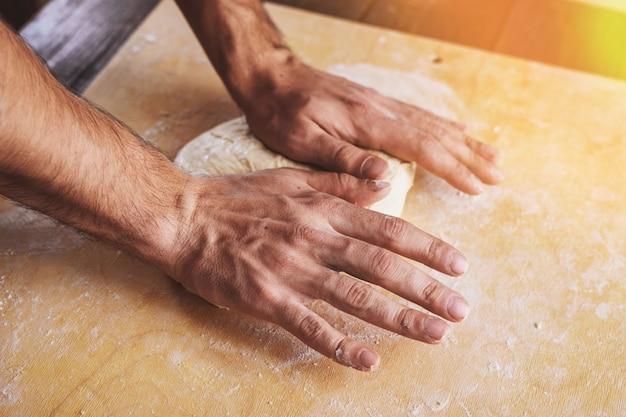 Close-up das mãos dos homens desenrolar, prepare a base para pizza.