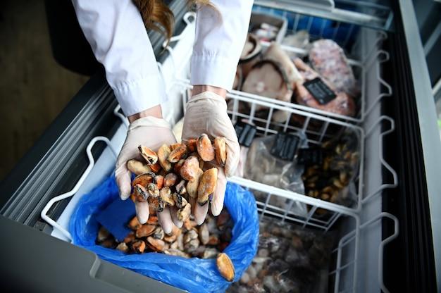 Close-up das mãos em luvas de borracha de um peixeiro na peixaria, tirando mexilhões do mar da geladeira cheia de frutos do mar congelados. vista de alto ângulo, vista superior.