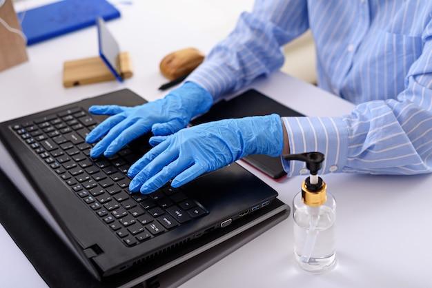 Close-up das mãos em luvas médicas azuis digitando no laptop, trabalho remoto em casa, freelancer no conceito de quarentena