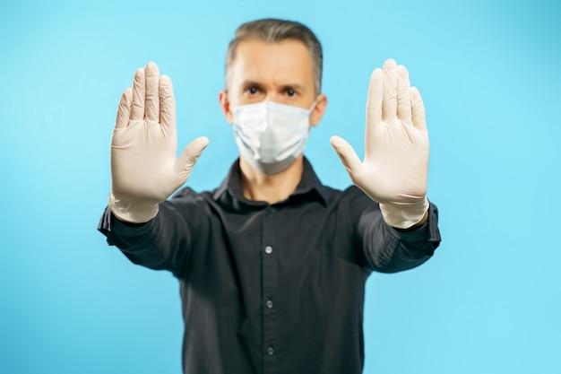 Close-up das mãos enluvadas de um jovem em uma máscara de proteção médica sobre um fundo azul. distância social. pare o gesto