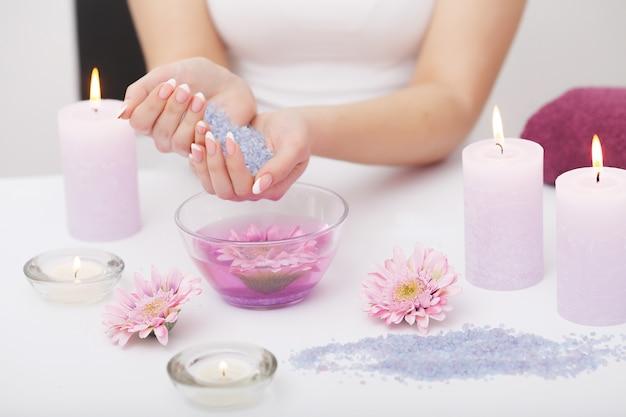 Close up das mãos fêmeas com as unhas naturais perfeitas que embebem no banho à mão antes do tratamento de mãos.