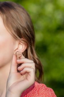 Close-up das mãos fêmeas que põem o aparelho auditivo na orelha. aparelho auditivo digital moderno no ouvido para surdez e pacientes com deficiência auditiva
