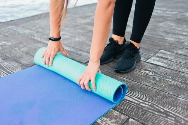 Close-up das mãos femininas cambaleando no tapete de ioga na praia.
