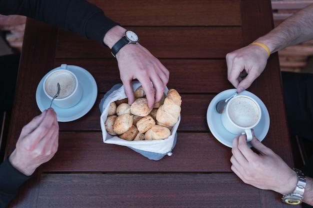 Close-up das mãos masculinas, bebendo café com biscoitos de queijo.
