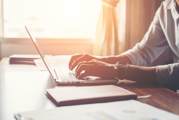 Close-up das mãos masculinas usando laptop em casa.