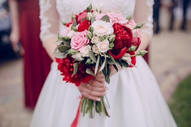 Close-up das mãos segurando o buquê de casamento